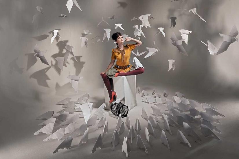 Une femme assise qui a libéré les oiseaux en papier de leur cage
